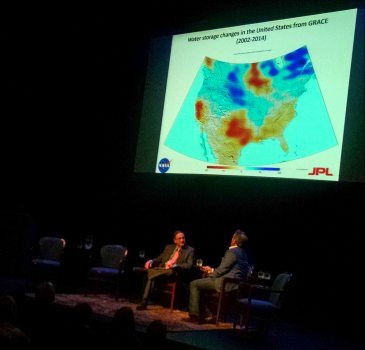 "NPR's Ira Flatow (left) and NASA water scientist Jay Famiglietti talked during Tuesday's discussion of ""Our Water: An Uncertain Future."" Famiglietti said red and yellow areas on the map are areas where water overuse is most critical. (David Boraks/WFAE)"