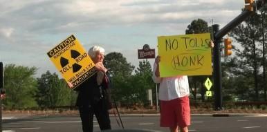 Anti-toll protesters held signs at Exit 28 in Cornelius in May 2015. (Lyndsay Kibiloski / CorneliusNews.net)