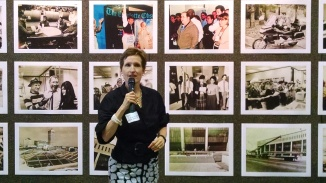 Current publisher Ann Caulkins spoke during Thursday's reception, in front of a wall of old photos. (David Boraks photo)