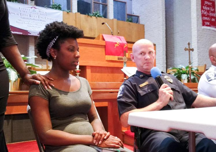 Aryana Crawford sits next to CMPD Capt. Chuck Henson at Wednesday's NAACP forum at Little Rock AME Zion Church. (David Boraks/WFAE)