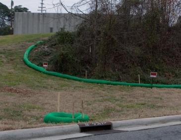 "Green ""filter socks"" are designed to control runoff behind the old Carolina Asbestos plant in Davidson. The trees will be removed and the hill full of asbestos covered starting next week. (David Boraks/WFAE)"