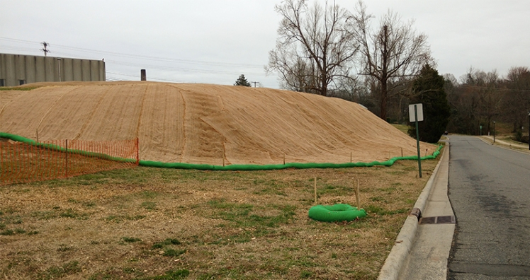 Workers cut down trees and shrubs then installed a plastic liner, soil and a fiber mat cover on this slope near the former Carolina Asbestos plant in Davidson. Last fall, environmental officials found asbestos running off from the hill. (David Boraks/ WFAE)