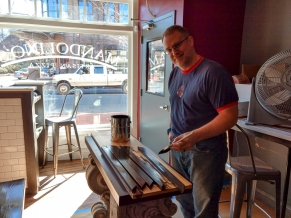 Partner Jason Tognarina paints shelving on Saturday. He's also the general manager at Flatiron Kitchen, across the street. (David Boraks photo)